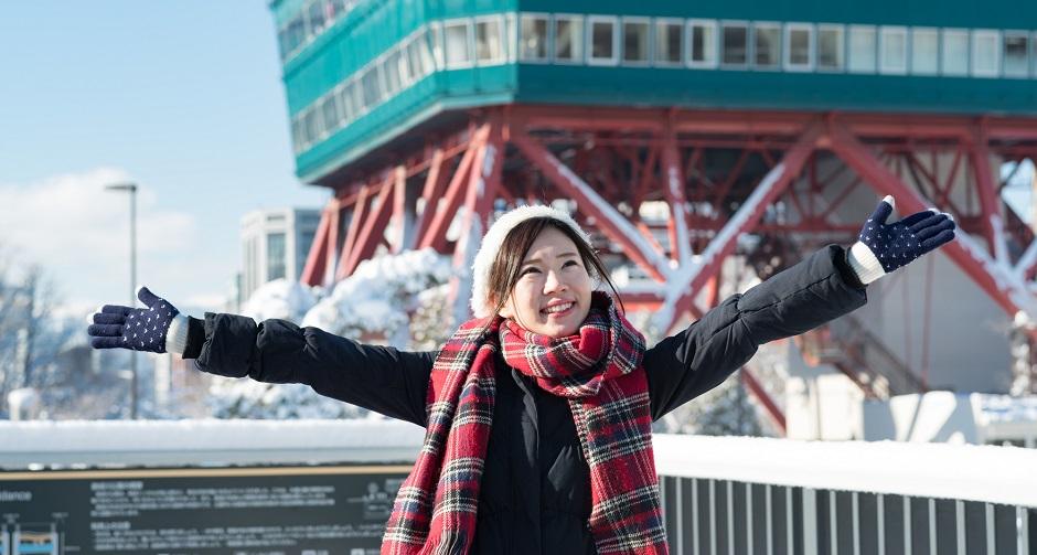 雪景色の東京タワーで手を広げて立つ女性