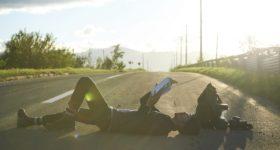 道路に寝そべって次の目的地の場所を探す男性