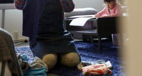 子どもの前で服を畳む男性