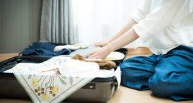 旅行に備えてスーツケースに服を詰める女性