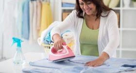 ポリエステルの服を洗濯して、アイロンでシワを伸ばす女性