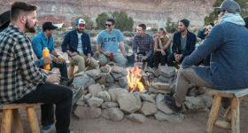 キャンプで火を囲む男女グループ
