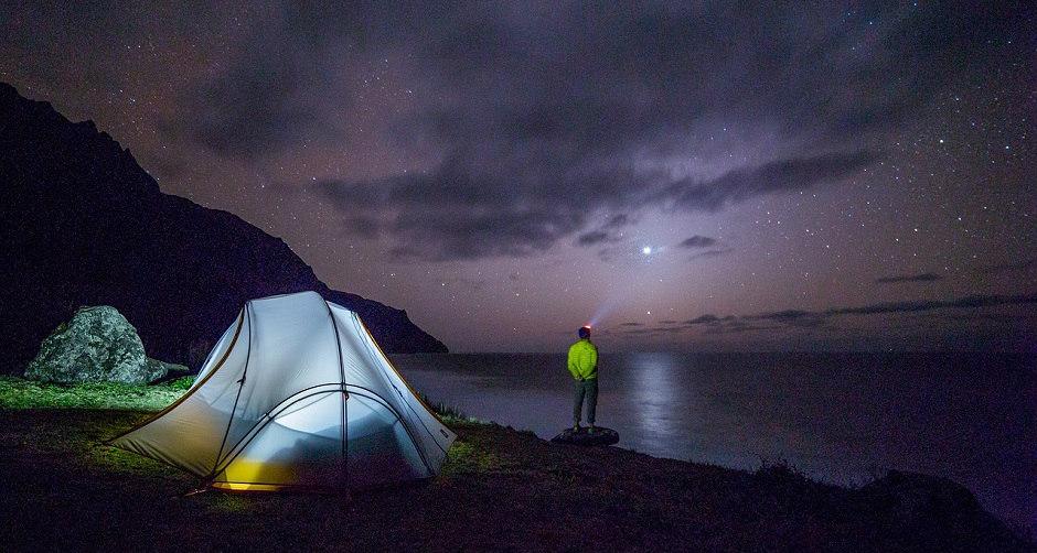 湖の前でキャンプ泊をする男性