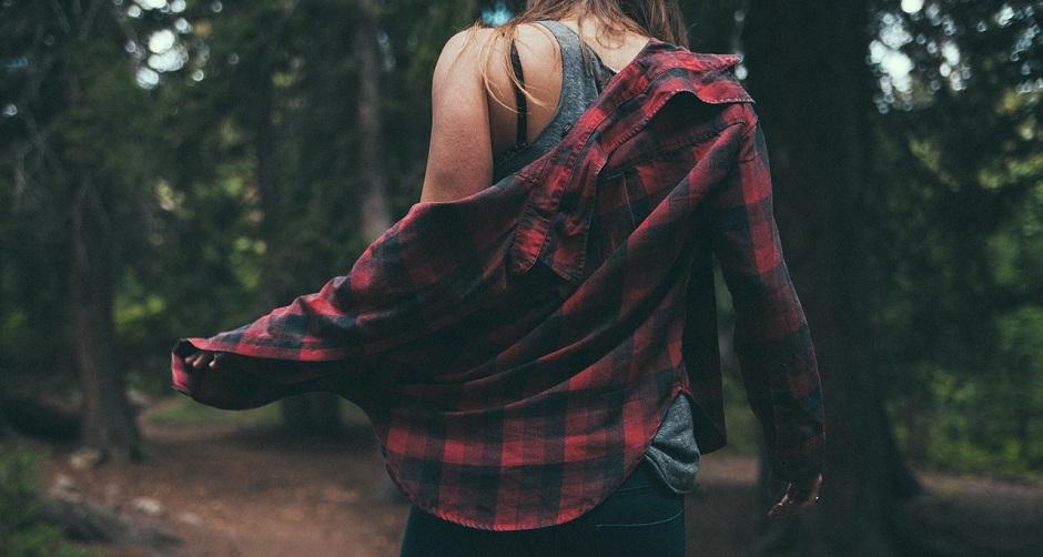 森の中でシャツを脱いでインナーを出す女性