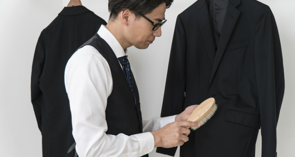 スーツにブラシをかける男性